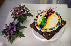 Delicious vanilla cake for children birthday party. Decorated with toys sport cars and chocolate cookies stock photos