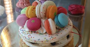 Delicious vanilla layered cake decorated macarons. Delicious vanilla layered cake decorated colored macarons stock footage