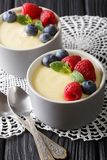 Delicious vanilla pudding with raspberries and blueberries close. Up on the table. vertical Stock Photography