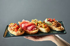 Delicious variety of Italian bruschetta on a ceramic tray. Holds the hand of man Stock Photos