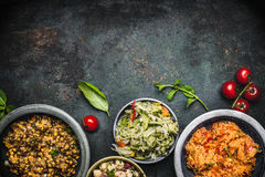 Delicious various vegetarian salads in bowls on dark rustic background, top view, border. Healthy eating. Vegetarian or vegan food concept Royalty Free Stock Images