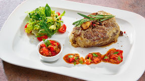 Delicious veal steak with salsa sauce and salad on a white plate.  royalty free stock images