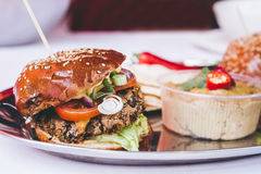 Delicious vegan black bean burger with vegetables and hummus, selective focus.  stock images