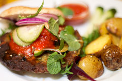Delicious vegan burger on white plate. Delicious vegan burger with chickpea patty, pickles, chili jam, mint, ketchup and baked potatoes on white plate Stock Photo