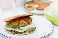 Delicious vegan burger on white plate. Delicious vegan burger with pea patty, grilled pear, grilled red preppers, shredded carrrot, iceberg salad, ketchup Royalty Free Stock Photography