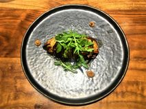 Delicious vegan food, turnip and rucola by chef Xavi Pellicer. Beautiful woodden table, art, decoration, healthy food, good taste and enchanting decoration in stock photo