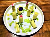 Delicious vegan food, white asparagus with flowers by chef Xavi Pellicer. Beautiful woodden table, art, decoration, healthy food, good taste and enchanting stock image