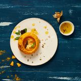 Delicious vegetable soup in pumpkin. Delicious vegetable soup decorated with basil leaves and cooked in pumpkin lying on flat round plate standing on blue aged Stock Images