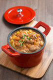 Delicious vegetable stew with sausages in a pan on wooden board Royalty Free Stock Photos