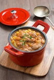 Delicious vegetable stew with sausages in a red pan Stock Photography