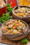 Delicious vegetable stew with sausages in wooden bowl, vertical Stock Image