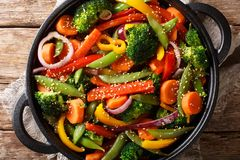 Delicious vegetarian vegetable stir fry with sesame close-up in a bowl, horizontal top view. Delicious vegetarian vegetable stir fry with sesame close-up in a stock images