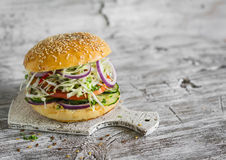 Delicious veggie burger with cabbage, tomato, cucumber, onions and peppers on a light wooden surface Royalty Free Stock Images