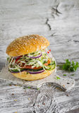 Delicious veggie burger with cabbage, tomato, cucumber, onions and peppers on a light wooden surface. Stock Photo