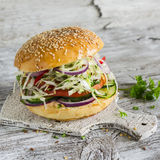 Delicious veggie burger with cabbage, tomato, cucumber, onions and peppers on a light wooden surface Stock Photos