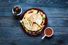 Delicious veggie quesadillas with tomatoes, olives, saòad and c. Heddar cheese in a colorful dish over a wooden Royalty Free Stock Photography