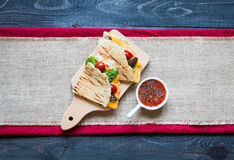 Delicious veggie quesadillas with tomatoes, olives, saòad and c. Heddar cheese in a colorful dish over a wooden Stock Images
