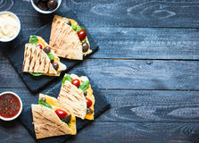Delicious veggie quesadillas with tomatoes, olives, salad. Delicious veggie quesadillas with tomatoes, olives, saòad and cheddar cheese in a colorful dish over Stock Image
