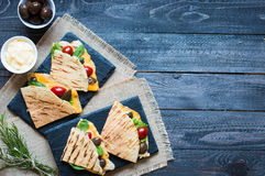 Delicious veggie quesadillas with tomatoes, olives, salad. Delicious veggie quesadillas with tomatoes, olives, saòad and cheddar cheese in a colorful dish over Royalty Free Stock Photography