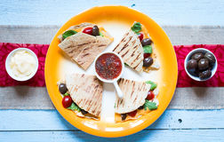Delicious veggie quesadillas with tomatoes, olives, salad. Delicious veggie quesadillas with tomatoes, olives, saòad and cheddar cheese in a colorful dish over Royalty Free Stock Photos