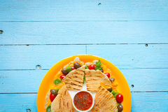 Delicious veggie quesadillas with tomatoes, olives, salad. Delicious veggie quesadillas with tomatoes, olives, saòad and cheddar cheese in a colorful dish over Royalty Free Stock Images