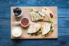 Delicious veggie quesadillas with tomatoes, olives, salad. Delicious veggie quesadillas with tomatoes, olives, saòad and cheddar cheese in a colorful dish over Stock Photos
