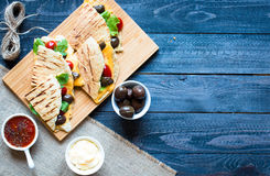 Delicious veggie quesadillas with tomatoes, olives, salad. Delicious veggie quesadillas with tomatoes, olives, saòad and cheddar cheese in a colorful dish over Stock Photo