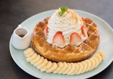 Delicious waffle with whipped cream and strawberry topping, eat stock photo