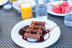 Delicious waffles with chocolate, water and juice Royalty Free Stock Photo