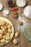 Delicious walnut shaped shortbread sandwich cookies filled with sweet condensed milk and chopped nuts on sackcloth background, vie stock photography