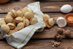 Delicious walnut shaped shortbread sandwich cookies filled with sweet condensed milk and chopped pistachio nuts. against. The background of the ingredients stock image