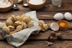 Delicious walnut shaped shortbread sandwich cookies filled with sweet condensed milk and chopped pistachio nuts on brown clay dish. On old wooden background Royalty Free Stock Photo