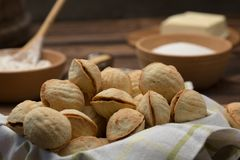 Delicious walnut shaped shortbread sandwich cookies filled with sweet condensed milk and chopped pistachio nuts on brown clay dish. On old wooden background Stock Photo