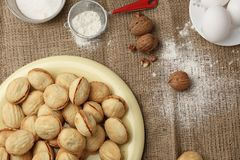 Delicious walnut shaped shortbread sandwich cookies filled with sweet condensed milk and chopped pistachio nuts on brown clay dish. On old wooden background Royalty Free Stock Photography
