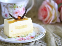Delicious white chocolate cake and a beautiful cup of tea for wonderful morning in soft blurred background Stock Images