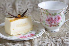 Delicious white chocolate cake and a beautiful cup of tea for wonderful morning in soft blurred background Stock Image