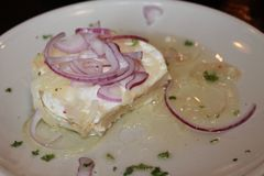 A bit of Camembert cheese pickled in oil with onion rings on a white plate royalty free stock photography