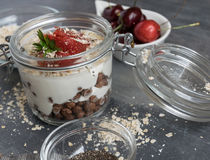 Delicious white yogurt in a glass with chocolate balls, oatmeal and fruit stock photography