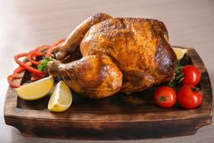 Delicious whole roasted chicken with vegetables. Served on wooden board Stock Images
