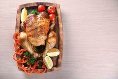 Delicious whole roasted chicken with vegetables served. On wooden board Stock Photos