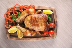 Delicious whole roasted chicken with vegetables served. On wooden board Royalty Free Stock Photos