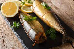 Delicious whole smoked mackerel with lemons and parsley closeup on a black slate board. horizontal royalty free stock photos