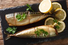 Delicious whole smoked mackerel with lemons and parsley closeup on a black slate board. Horizontal top view stock images