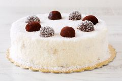 Delicious whole white cake with desiccated coconut powder and cocoa balls icing stock images