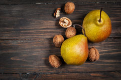 Delicious Williams pears and walnuts on a rustic wooden table Royalty Free Stock Image