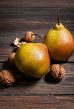 Delicious Williams pears and walnuts on a rustic wooden table Royalty Free Stock Photos
