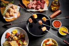 Delicious winter fondue with assorted meat. Delicious winter fondue with assorted cubed fresh meat, vegetable and pickle salad and dipping sauces viewed from royalty free stock photography
