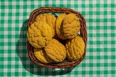 Delicious yellow cookie of corn on basket and green plaid table. Sweet food of Festa Junina, a typical brazilian party, holiday event in June Stock Image