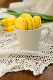 Delicious yellow macaroon and yellow tulips Royalty Free Stock Images