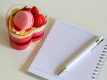Delicious yogurt cake Colorful yogurt cake with pen on notebook. Colorful yogurt cake with pen on notebook Royalty Free Stock Photography